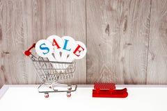 Καροτσάκι αγορών με τα κιβώτια δώρων σε ένα ξύλινο υπόβαθρο Πώληση διακοπών Στοκ Εικόνα