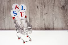 Καροτσάκι αγορών με τα κιβώτια δώρων σε ένα ξύλινο υπόβαθρο Πώληση διακοπών Στοκ Εικόνες