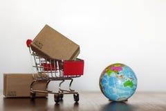 Καροτσάκι αγορών με τη σφαίρα χαρτοκιβωτίων και γης Επιχειρησιακή έννοια παγκοσμίως αγορών και παράδοσης στοκ φωτογραφίες με δικαίωμα ελεύθερης χρήσης