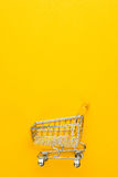 Καροτσάκι αγορών στο κίτρινο υπόβαθρο Στοκ φωτογραφία με δικαίωμα ελεύθερης χρήσης