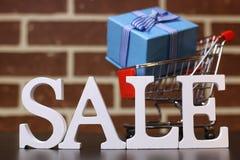Καροτσάκι για τα προϊόντα σε μια νέα πώληση έτους ` s υποβάθρου τουβλότοιχος Στοκ φωτογραφίες με δικαίωμα ελεύθερης χρήσης