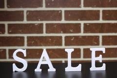 Καροτσάκι για τα προϊόντα σε μια νέα πώληση έτους ` s υποβάθρου τουβλότοιχος Στοκ Εικόνες