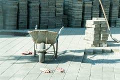 Καροτσάκι κατασκευής με τα γάντια εργαζομένων και πέτρα πεζοδρομίων στο υπόβαθρο στην περιοχή επίστρωσης οδών Στοκ εικόνα με δικαίωμα ελεύθερης χρήσης