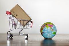 Καροτσάκι με τη σφαίρα χαρτοκιβωτίων και γης Επιχειρησιακή έννοια παγκοσμίως αγορών και παράδοσης στοκ φωτογραφίες