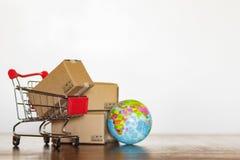 Καροτσάκι με τη σφαίρα χαρτοκιβωτίων και γης Επιχειρησιακή έννοια παγκοσμίως αγορών και παράδοσης στοκ φωτογραφία με δικαίωμα ελεύθερης χρήσης