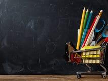 Καροτσάκι με τις σχολικές προμήθειες στο υπόβαθρο ενός πίνακα στοκ εικόνες