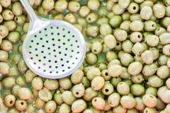 Καρυκευμένες πράσινες ελιές με μια κουτάλα Στοκ εικόνα με δικαίωμα ελεύθερης χρήσης