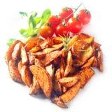 Καρυκευμένες σφήνες πατατών με τις ντομάτες κερασιών Στοκ εικόνα με δικαίωμα ελεύθερης χρήσης