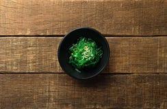 Καρυκευμένη ιαπωνική σαλάτα φυκιών σουσαμιού στο μαύρα κύπελλο και το ξύλο Στοκ φωτογραφία με δικαίωμα ελεύθερης χρήσης