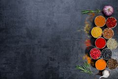 Καρυκεύματα ζωηρόχρωμα καρυκεύματα Κάρρυ, σαφράνι, turmeric, κανέλα και otheron ένα σκοτεινό συγκεκριμένο υπόβαθρο Πιπέρι Μεγάλη  Στοκ Φωτογραφίες