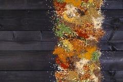 Καρυκεύματα και χορτάρια στο σκοτεινό ξύλινο υπόβαθρο Διάστημα για το κείμενο Πλαίσιο τροφίμων Τοπ άποψη με το διάστημα αντιγράφω Στοκ Εικόνες