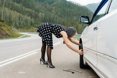 Καρφίτσα-επάνω στη μεταβαλλόμενη ρόδα αυτοκινήτων γυναικών στο δρόμο στοκ εικόνες