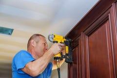 Καρφί ξυλουργών που χρησιμοποιεί το πυροβόλο όπλο καρφιών για να στέψει το σχήμα στα γραφεία κουζινών που πλαισιώνουν την περιποί Στοκ φωτογραφία με δικαίωμα ελεύθερης χρήσης
