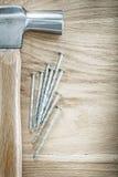 Καρφιά κατασκευής σφυριών νυχιών στην ξύλινη έννοια οικοδόμησης πινάκων Στοκ Φωτογραφίες