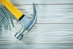 Καρφιά κατασκευής σφυριών νυχιών στον ξύλινο πίνακα Στοκ εικόνες με δικαίωμα ελεύθερης χρήσης