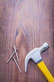 Καρφιά σφυριών νυχιών στον εκλεκτής ποιότητας ξύλινο πίνακα με Στοκ Εικόνες