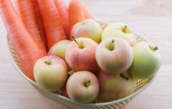Καρότα και μήλα σε ένα καλάθι Στοκ Εικόνες
