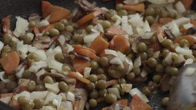 Καρότα με τα μανιτάρια κρεμμυδιών και πράσινα μπιζέλια στα τηγανητά σε ένα τηγάνι απόθεμα βίντεο
