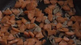 Καρότα με τα μανιτάρια στα τηγανητά σε ένα τηγάνι φιλμ μικρού μήκους