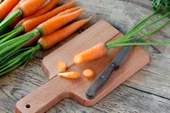 Καρότο στον τέμνοντα πίνακα με το μαχαίρι Στοκ Φωτογραφίες