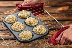 Καρότο cupcakes με το λεμόνι και το μήλο, αμύγδαλα στο ξύλινο υπόβαθρο, ακατέργαστη μορφή σιλικόνης σε ένα φύλλο ψησίματος Στοκ εικόνες με δικαίωμα ελεύθερης χρήσης