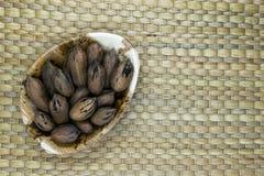 Καρύδια πεκάν με το κέλυφος στο φυσικό πιάτο φύλλων μπανανών Eco στη φυσική επιφάνεια χαλιών μπαμπού με ελεύθερου χώρου Στοκ φωτογραφία με δικαίωμα ελεύθερης χρήσης