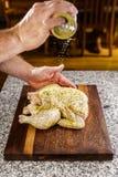 Καρύκευση ολόκληρου ενός κοτόπουλου για το ψήσιμο στη σχάρα Στοκ Εικόνες