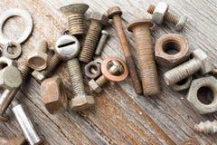 Καρύδια, μπουλόνια σε ένα shabby ξύλινο υπόβαθρο Στοκ Εικόνες