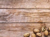 καρύδια Ολόκληρα και ξεφλουδισμένα ξύλα καρυδιάς στο ξύλινο υπόβαθρο στοκ φωτογραφία με δικαίωμα ελεύθερης χρήσης