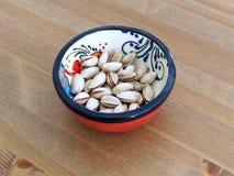 Καρύδια φυστικιών στο κόκκινο ισπανικό κύπελλο Στοκ εικόνα με δικαίωμα ελεύθερης χρήσης