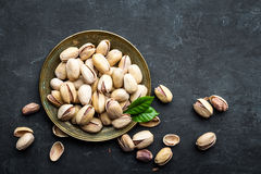 Καρύδια φυστικιών στο σκοτεινό υπόβαθρο, τοπ άποψη, υγιές πρόχειρο φαγητό στοκ εικόνες