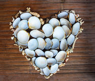 Καρδιά από τα άσπρα κοράλλια και τα κοχύλια στο ξύλινο υπόβαθρο Χειροποίητο ντεκόρ αγάπης από την εύρεση παραλιών Στοκ Εικόνες