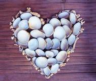 Καρδιά από τα άσπρα κοράλλια και τα κοχύλια στο ξύλινο υπόβαθρο Χειροποίητο ντεκόρ αγάπης από την εύρεση παραλιών Στοκ Φωτογραφία