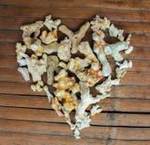 Καρδιά από τα άσπρα κοράλλια στο ξύλινο υπόβαθρο Χειροποίητο ντεκόρ αγάπης από την εύρεση παραλιών Στοκ Εικόνα