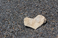 Καρδιά από την ελαφριά πέτρα στις σκοτεινές πέτρες Στοκ Φωτογραφία