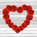 Καρδιά ημέρας βαλεντίνων φιαγμένη από κόκκινα τριαντάφυλλα στο άσπρο ξύλινο backgroun Στοκ εικόνα με δικαίωμα ελεύθερης χρήσης