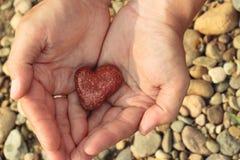 Καρδιά-διαμορφωμένη πέτρα στα χέρια Στοκ φωτογραφία με δικαίωμα ελεύθερης χρήσης