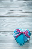 Καρδιά-διαμορφωμένο μπλε παρόν κιβώτιο με τη ρόδινη κορδέλλα στον ξύλινο πίνακα CEL Στοκ Εικόνα