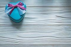 Καρδιά-διαμορφωμένο μπλε παρόν κιβώτιο με το ρόδινο τόξο στο ξύλινο holi πινάκων Στοκ φωτογραφία με δικαίωμα ελεύθερης χρήσης