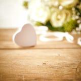 Καρδιά καραμελών στον ξύλινο πίνακα με την άσπρη ροδαλή ανθοδέσμη Στοκ φωτογραφίες με δικαίωμα ελεύθερης χρήσης