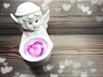 Καρδιά κρυστάλλου εκμετάλλευσης παιχνιδιών αγγέλου στα χέρια στο ξύλινο υπόβαθρο Στοκ φωτογραφία με δικαίωμα ελεύθερης χρήσης