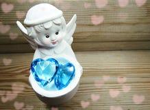 Καρδιά κρυστάλλου εκμετάλλευσης παιχνιδιών αγγέλου στα χέρια στο ξύλινο υπόβαθρο Στοκ Φωτογραφίες