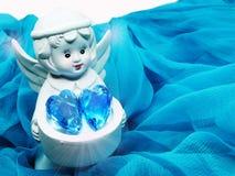 Καρδιά κρυστάλλου εκμετάλλευσης παιχνιδιών αγγέλου στα χέρια στο μεταξωτό υπόβαθρο Στοκ Φωτογραφίες
