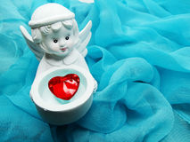 Καρδιά κρυστάλλου εκμετάλλευσης παιχνιδιών αγγέλου στα χέρια στο μεταξωτό υπόβαθρο Στοκ Φωτογραφία