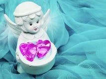 Καρδιά κρυστάλλου εκμετάλλευσης παιχνιδιών αγγέλου στα χέρια στο μεταξωτό υπόβαθρο Στοκ Εικόνες
