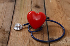 Καρδιά με ένα στηθοσκόπιο, που απομονώνεται στο ξύλινο υπόβαθρο Στοκ Εικόνες