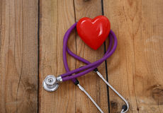 Καρδιά με ένα στηθοσκόπιο, που απομονώνεται στο ξύλινο υπόβαθρο Στοκ Φωτογραφία