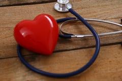 Καρδιά με ένα στηθοσκόπιο, που απομονώνεται στο ξύλινο υπόβαθρο Στοκ Φωτογραφίες