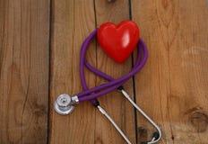 Καρδιά με ένα στηθοσκόπιο, που απομονώνεται στο ξύλινο υπόβαθρο Στοκ εικόνα με δικαίωμα ελεύθερης χρήσης