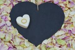 Καρδιά με τα πέταλα τριαντάφυλλων και το χρυσό δαχτυλίδι Στοκ εικόνες με δικαίωμα ελεύθερης χρήσης